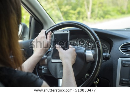women driver with a cell phone in hand while driving.