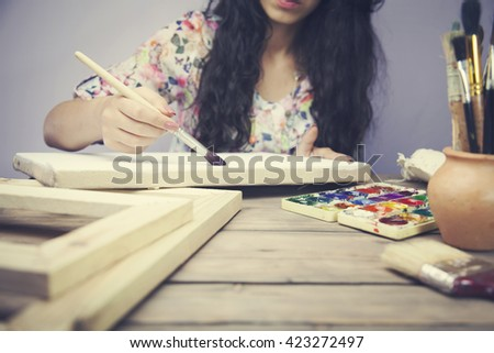 women hand with brush drawing on canvas