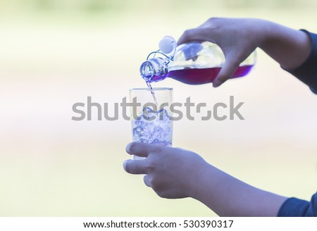 women Handle holding Ice water italian soda purple in glass cup , Ice butterfly beverage healthy