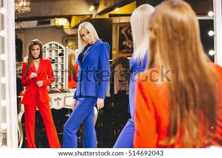 Women posing in red and blue suits