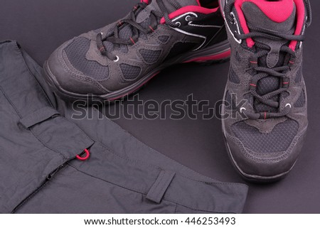 Women's hiking boots and trousers on black background
