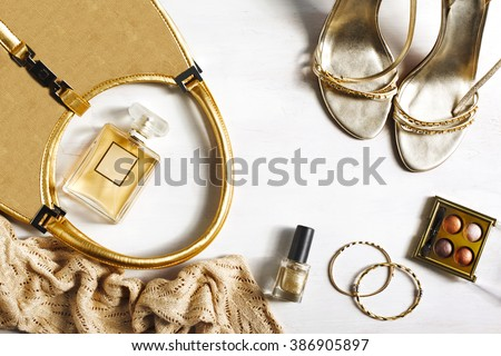 Women's set of fashion accessories in golden color on wooden background: shoes, handbag, perfume and cosmetics