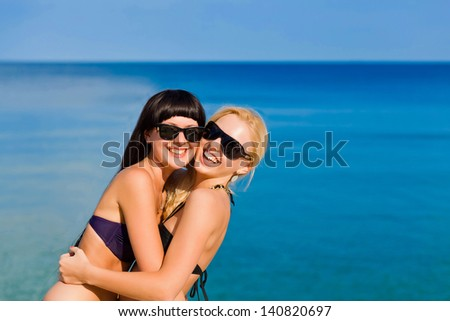 Womens in bikini stands in front of the sea. Summer.
