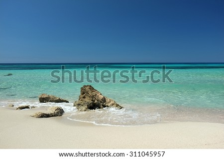 Wonderful sandy beach with some rocks and turquoise clear water