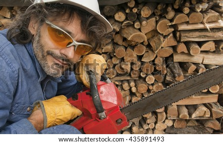 woodcutter with chainsaw looking at camera