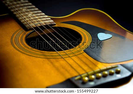 Wooden acoustic guitar with blue pick