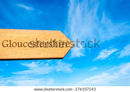 Wooden arrow sign pointing destination Gloucestershire, ENGLAND against clear blue sky with copy space available. Travel destination conceptual image
