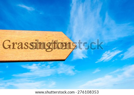 Wooden arrow sign pointing destination GRASSINGTON, ENGLAND against clear blue sky with copy space available. Travel destination conceptual image