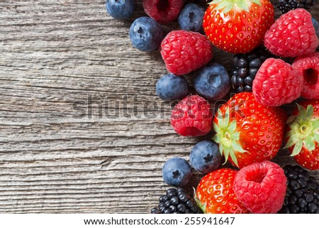wooden background with fresh berries, top view