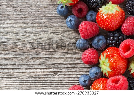 wooden background with fresh berries, top view, horizontal