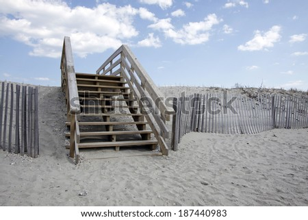 Wooden Beach Access Stairway Going Up Over A Sand Dune With Dune Fence And  Blue Sky