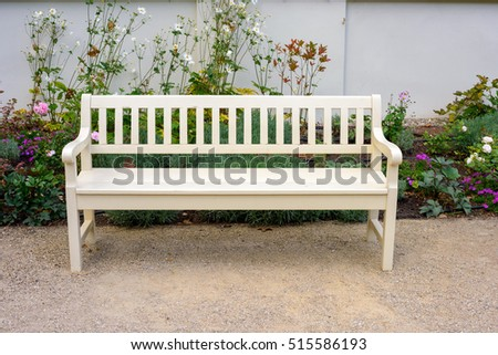 wooden bench and flowers in garden in the morning