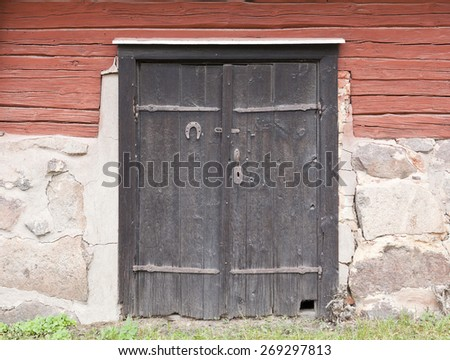 Wooden black doors on a warehouse. Timber, logs on the stone basement.