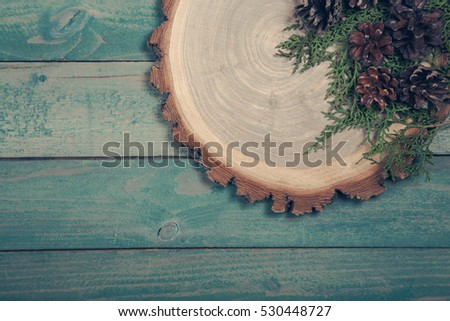 Wooden board with leaves of thuja and pine cones on the table