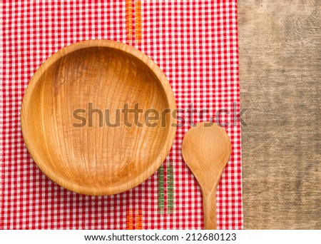 Wooden bowl and wooden spoon on rustic wooden table