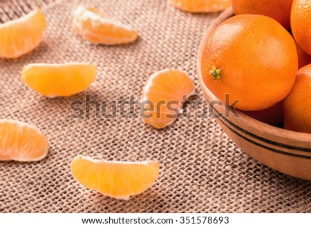 Wooden bowl filled with fruit mandarins with scattered slices on sackcloth