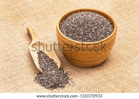 Wooden bowl full with chia seeds and a spoon next to it on sack cloth background seen from above