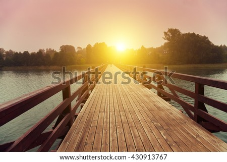 Wooden bridge over lake in early misty morning