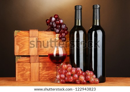 Wooden cases with wine bottles on wooden table on brown background