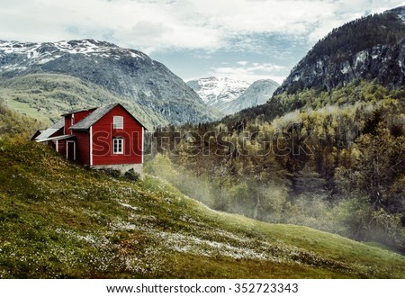 Wooden cottage valley flowers stone snowy stock photo for Cottage in the mountains