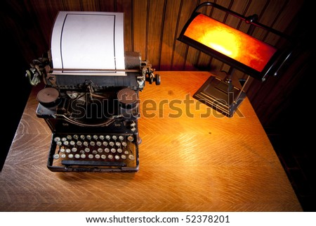 Wooden desk lit up by an old lamp with yellow light and a historic rusty typewriter with a plasticized sheet of white paper.