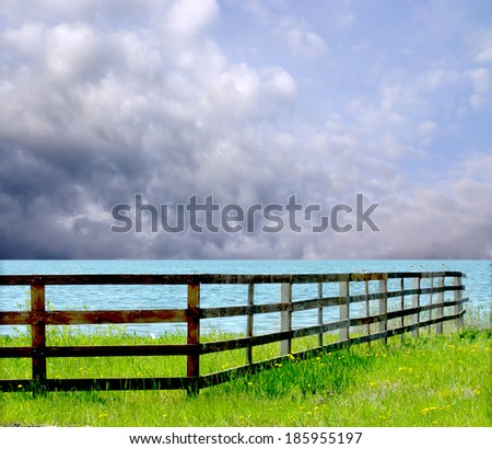wooden fence on the river on a background of blue sky with clouds