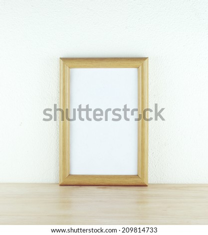 Wooden frame on table over cement wall.