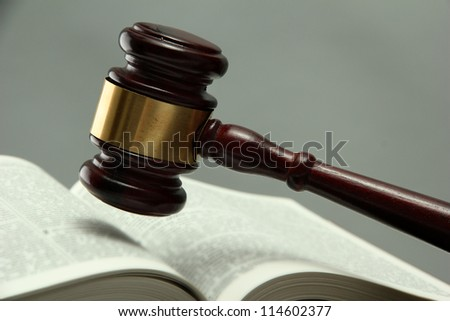 wooden gavel and book, on grey background