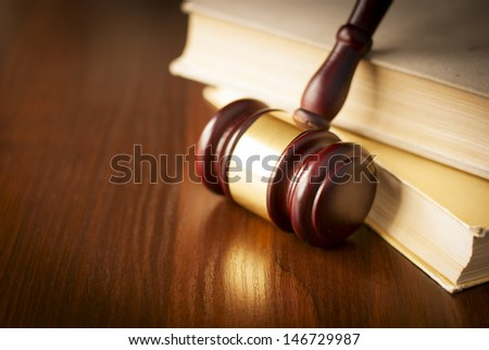 Wooden gavel in a courtroom standing upright against a stack of law books on the judges desk