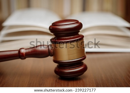 Wooden gavel resting on its end on a wooden table in front of an open law book conceptual of a judge, courtroom and judgements
