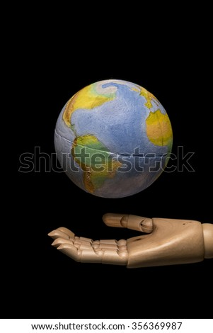 Wooden hand supports the world. Studio shot on black background