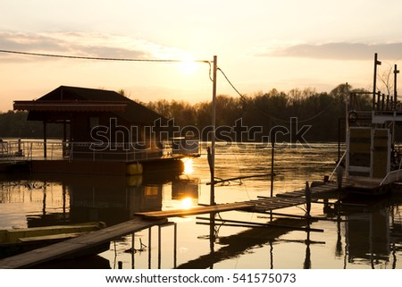 Wooden house and raft on the river reflecting out of water at sunset