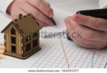 wooden house in the graphs and male hand with phone doing records