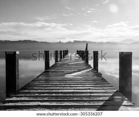 wooden jetty at a little lake in upper bavaria with mountains in background