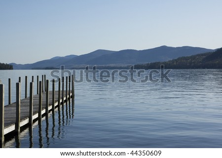 Wooden jetty reaching out to Lake George with the mountains in the background across the lake.