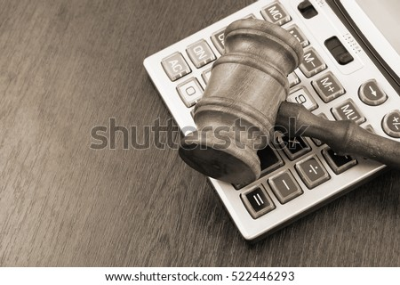 Wooden judge gavel and calculator, arbitration concept