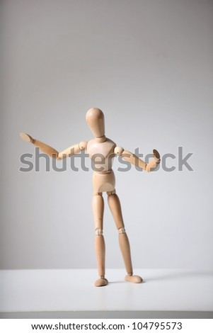 wooden man dancing and playing sports on a gray background