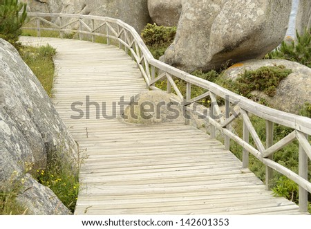 "Wooden pathway in a natural park with green trees and big rocks. ""Rias Baixas"", Galicia, Spain."