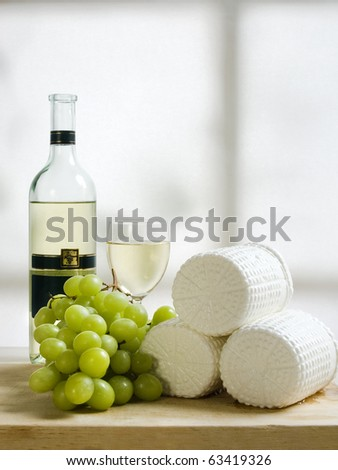 wooden plate of cheese grapes and wine