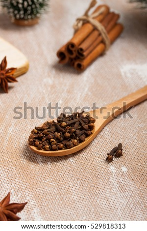 Wooden spoon with cloves, cinnamon, star anise on wooden background