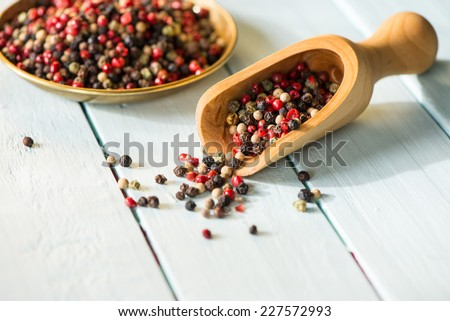 Wooden spoon with colorful chili seeds on white table