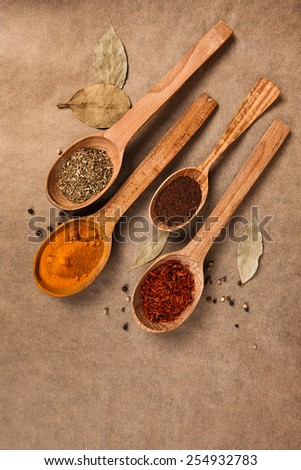 wooden spoon with spices on brown background