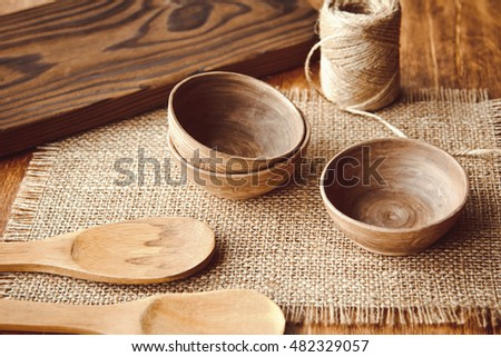 Wooden spoons and bowls on the background of burlap on the table