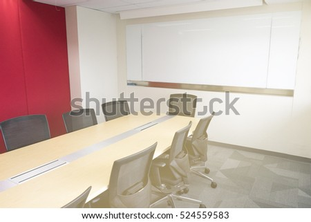 wooden table in meeting room white board sunlight from window