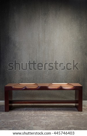 Wooden waiting bench on concrete floor against concrete wall