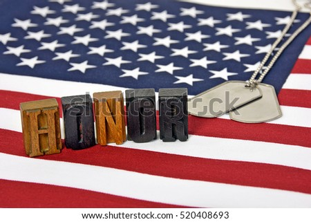 word honor in vintage wooden letterpress type on American flag with military dog tags