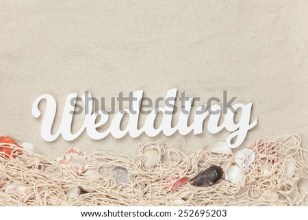 Word Wedding and net with shells on sand background.