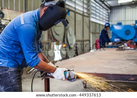 Worker cutting metal with grinder in the factory.