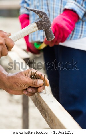 Worker hammering nail into wood at construction site