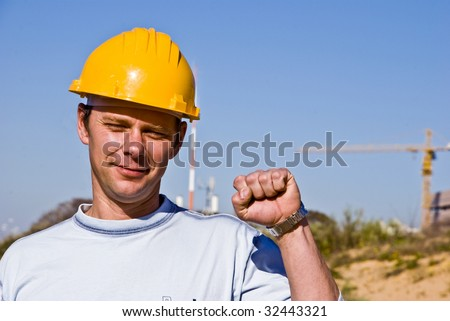 Worker in a hard hat raising his hand as a sign of success.